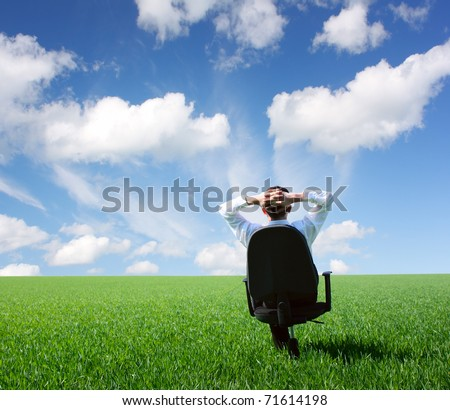 Businessman sitting on chair in green meadow and looking to a blue cloudy sky - stock photo