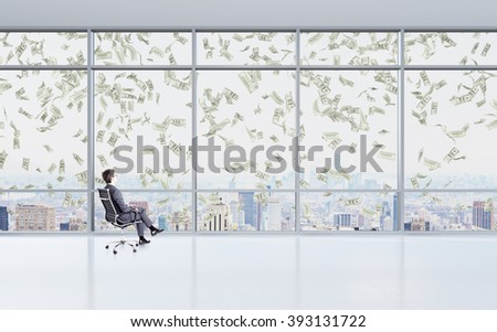 Businessman sitting on chair. Panoramic window with New York view in front, dollars falling from above. Concept of earning money. - stock photo