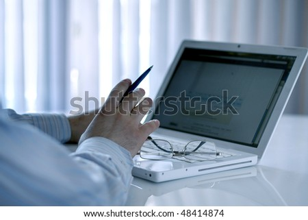 businessman sitting on couch using laptop - stock photo