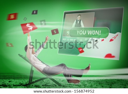Businessman sitting on deck chair looking at holographic screen in green light on the beach - stock photo