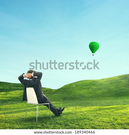 Businessman sitting on green field and looking at air balloon - stock photo