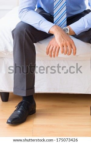 Businessman sitting on his bed at home in bedroom