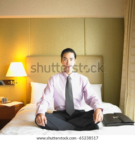 Businessman sitting on hotel room bed