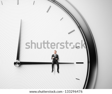 Businessman sitting on minute hand with cup of coffee - stock photo