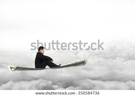 Businessman sitting on money flying carpet, with cloudscape background. - stock photo