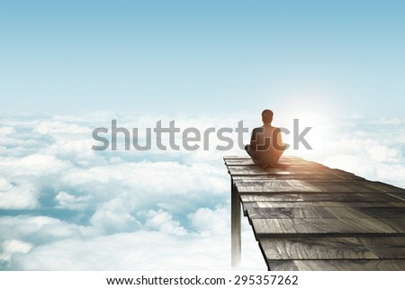 businessman sitting on pier and looking clouds - stock photo