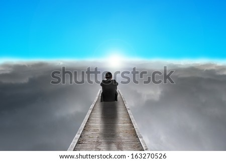 businessman sitting on pier looking sunrise with dark clouds and blue sky