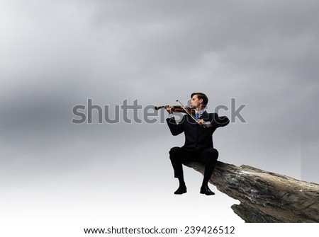Businessman sitting on rock edge and playing violin