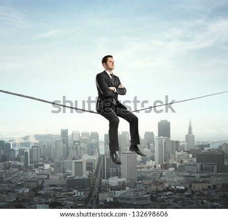 businessman sitting on rope and city - stock photo
