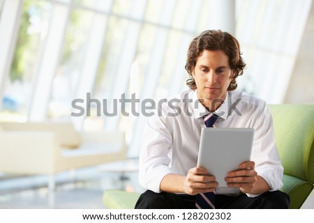 Businessman Sitting On Sofa In Office Using Digital Tablet - stock photo