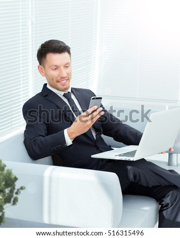 businessman sitting on sofa in the office, keep a laptop open and dials the number on the smartphone