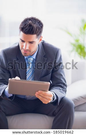Businessman sitting on sofa using his tablet pc in the office - stock photo