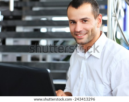 Businessman sitting on stairs and using laptop pc - stock photo