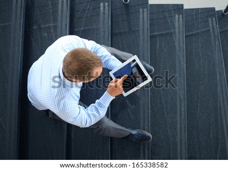 businessman sitting on stairs with electronic tablet  - stock photo