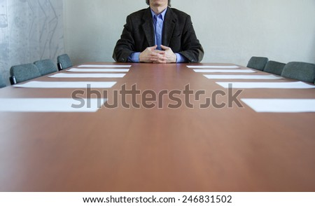 businessman sitting on table in office - stock photo