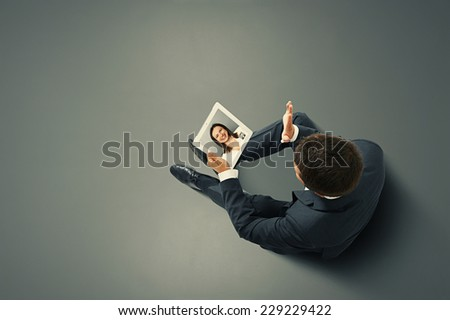 businessman sitting on the floor, holding tablet pc and waving his hand to young smiley woman. photo in the dark room - stock photo