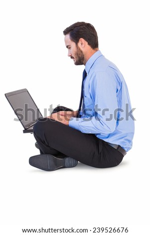 Businessman sitting on the floor using his laptop on white background