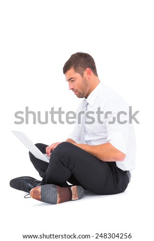 Businessman sitting on the floor using laptop on white background