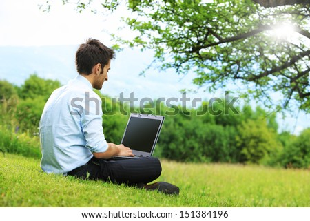Businessman sitting on the grass is working on laptop - stock photo