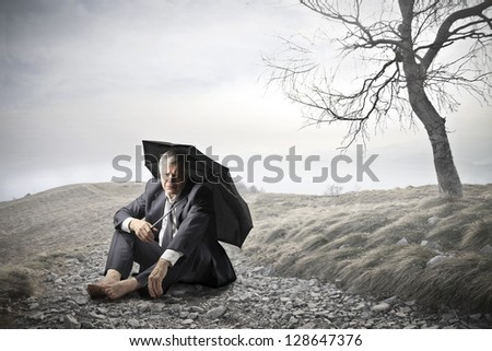 businessman sitting on the ground with umbrella - stock photo
