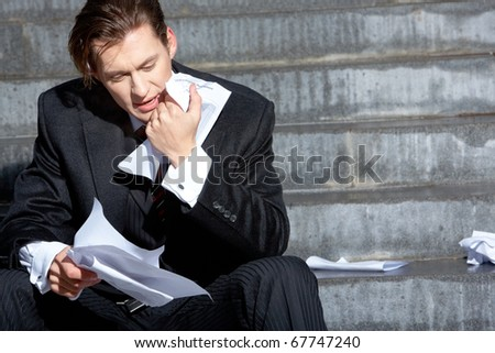 Businessman sitting on the stairs of building and looking at document - stock photo