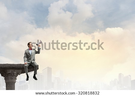 Businessman sitting on top and screaming in megaphone - stock photo