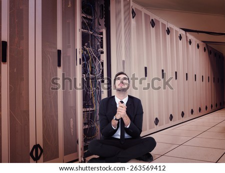 Businessman sitting praying and looking up against data center - stock photo