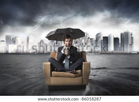 Businessman sitting under an umbrella on an armchair with cityscape in the background - stock photo