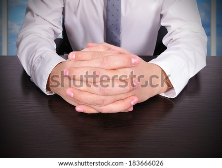 businessman sitting with crossed fingers - stock photo