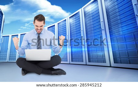 Businessman sitting with his laptop cheering against composite image of server towers - stock photo