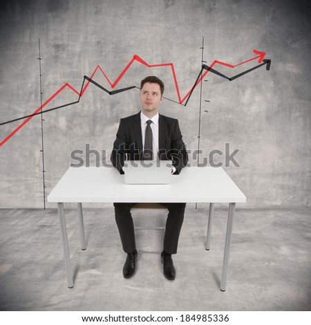 businessman sitting with laptop and drawing chart on wall