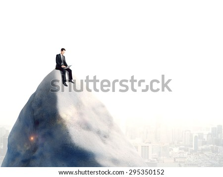 businessman sitting with notebook on top of mountain - stock photo