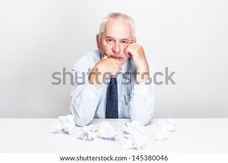 Businessman sitting with paperwork at desk in office - stock photo