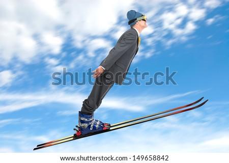 Businessman ski jumping against the sky - stock photo