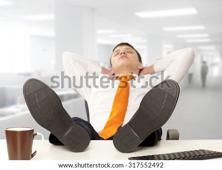 Businessman sleeping. Businessman reclining with his feet up on desk in office - stock photo