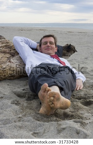 Businessman sleeping on a beach with a smile on his face - stock photo
