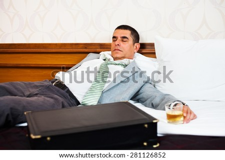 Businessman sleeping on a bed, holding glass of whiskey - stock photo