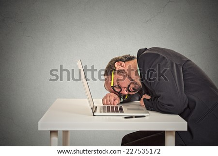 Businessman sleeping on a laptop, tired middle aged guy employee isolated on grey office wall background. Sleep deprivation, long working hours concept  - stock photo
