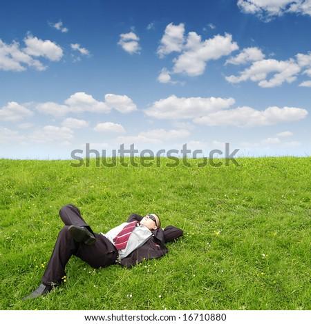 businessman sleeping on green grass - stock photo