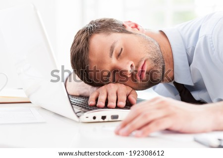 Businessman sleeping. Side view of young man in shirt and tie sleeping while sitting at his working place - stock photo