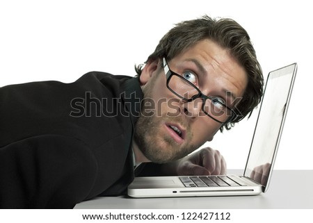 Businessman slightly leaning on his laptop looking shocked on what we see on his back