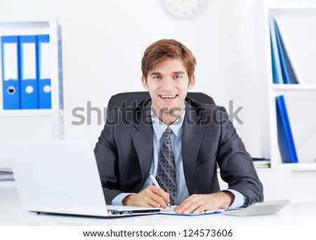 businessman smile at office desk sign up contract, Handsome young business man sitting working with documents, papers, business plan, handwriting - stock photo