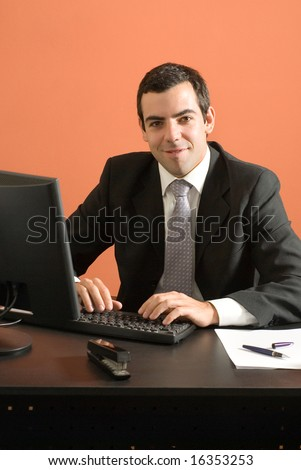 Businessman smiles as he sits at his desk and works on his computer. Vertically framed photo. - stock photo