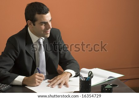 Businessman smiles as he works at his desk. Horizontally framed photo. - stock photo