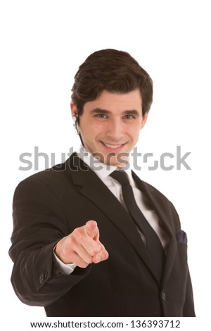 Businessman smiling and pointing forwards towards the camera with his finger isolated on white