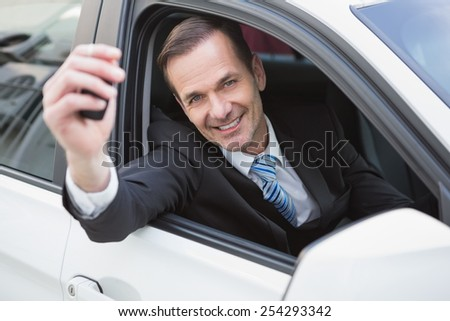 Businessman smiling and showing key in his car - stock photo