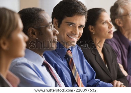 Businessman smiling at a meeting - stock photo