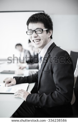 Businessman smiling at the camera while his team is working in the background.Asian - stock photo