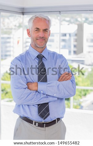 Businessman smiling with arms crossed in his office - stock photo