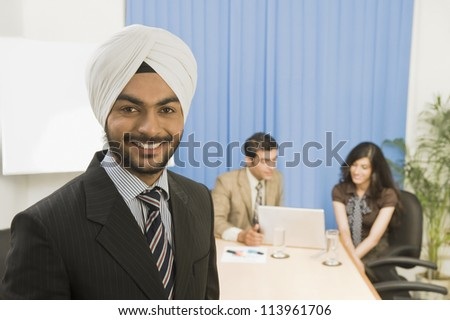 Businessman smiling with his colleagues in the background - stock photo